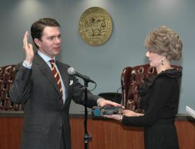 Corporation Commission Chair, Bob Stump, taking the oath of office.  His mother Jane Stump is holding the Bible.