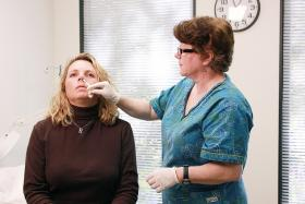 A nurse administering FluMist® live attenuated intranasal vaccine LAIV) into this patient's nasal cavity.