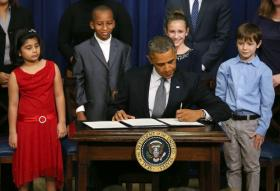 U.S. President Barack Obama signs a series of executive orders about the administration's new gun law proposals as children who wrote letters to the White House about gun violence, (L-R) Hinna Zeejah, Taejah Goode, Julia Stokes and Grant Fritz, look on in the Eisenhower Executive Office building, on January 16, 2012 in Washington, DC.