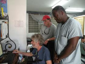 Left to right: Doctors John Durham, Steve Schoering and Alexandre Schiller consult on a patient case, Port au Prince, Haiti