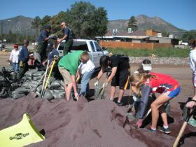 Volunteers create sandbags to protect homes from flooding in the Shultz burn area.