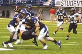 The NAU football team tackles a player from Portland State