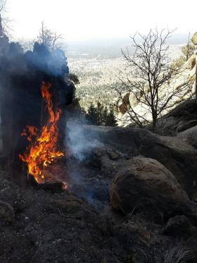 A stump burns in Paradise Canyon on the Boulder Fire.