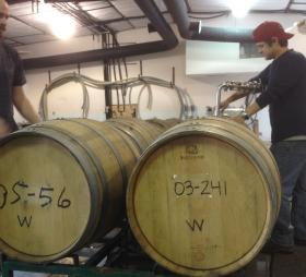 Niles Johnson (left) and Joseph Ranallo rack barrels of white wine.