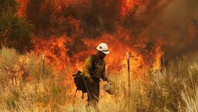 A firefighter sets a backburn during a 2011 eastern Arizona wildfire.