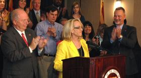 House Speaker Andy Tobin and Charles Flanagan, director of the new Department of Child Safety, cheer Gov. Jan Brewer for signing legislation to create the agency and boost funding.