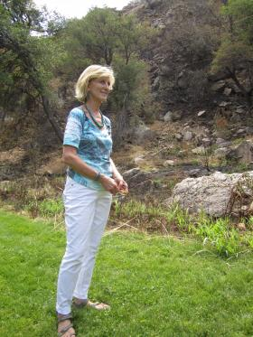 Mary Garland, owner of Garland's Lodge, stands near her property line where the Slide Fire stopped its advance.