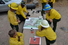 Members of the Burned Area Emergency Response team go over a map of the forest areas receiving the mulch treatments.