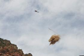 A helicopter scattering mulch just above its target in Oak Creek Canyon.