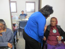 While Coconino County Supervisor Lena Fowler greets Lola Bennett in her crowded Tuba City office, Matilda Perdue (in the office behind) meets with clients to help them navigate through the complicated process of applying for delayed birth certificates.
