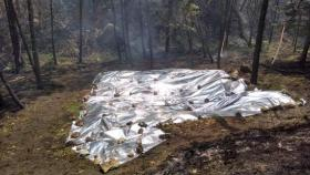 During the Slide Fire, crews covered the cabin site with a protective flame-resistant blanket.