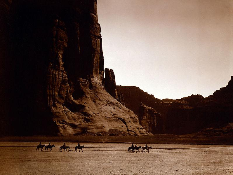 Seven Navajo riders on horseback in Canyon de Chelly in the early 1900s.
