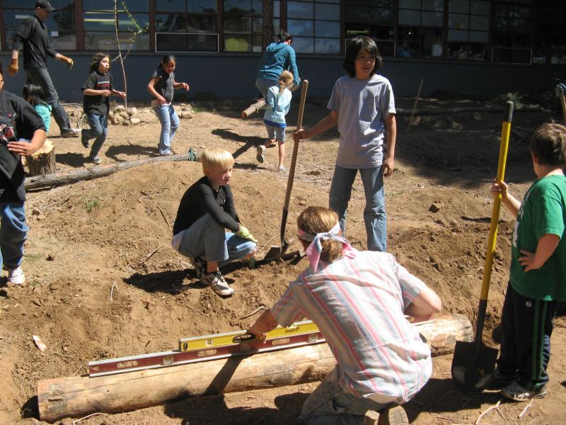 Students at Puente de Hozho elementary school build garden terraces. They recycled the logs from forest thinning projects in Flagstaff.