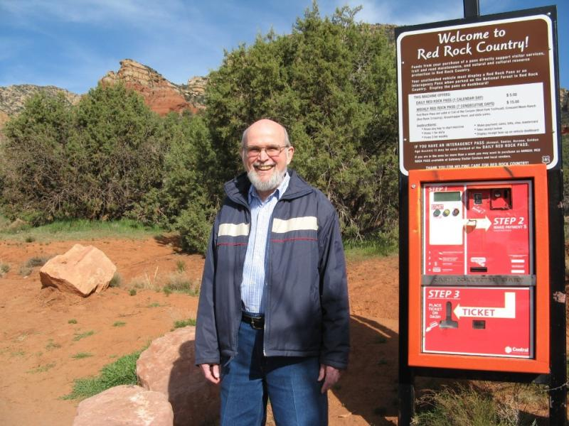 Jim Smith standing next to a Red Rock Pass dispenser at a trailhead outside Sedona.