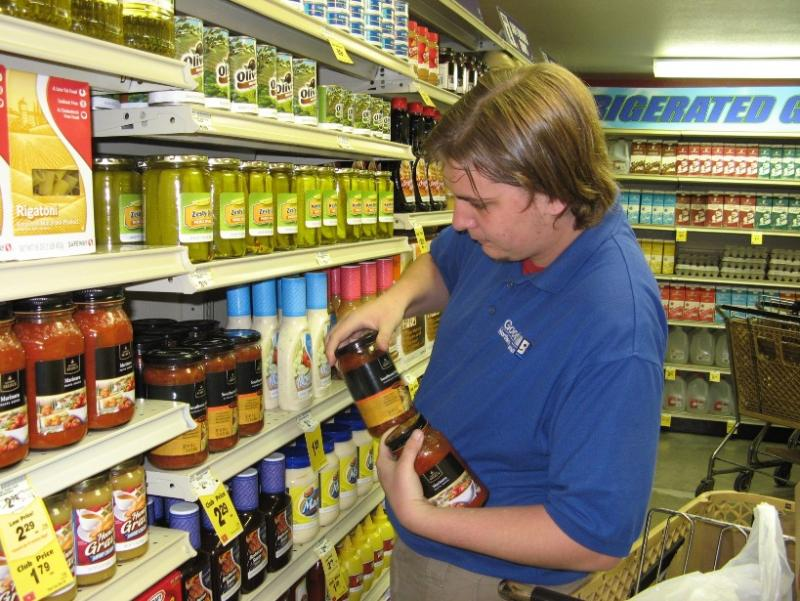 """William West practices stocking shelves at a \""""mini\"""" Safeway training center at Goodwill Industries in Flagstaff."""