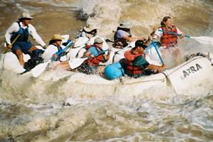 A group paddles through a white-water rapid in Grand Canyon.