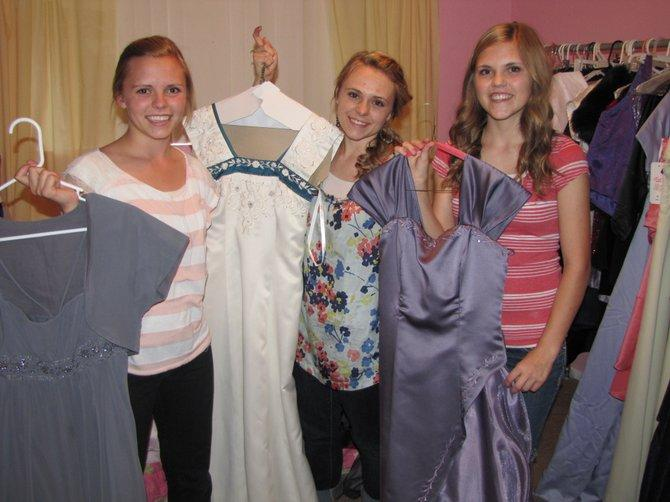 The Fuller sisters hold up the donated dresses.
