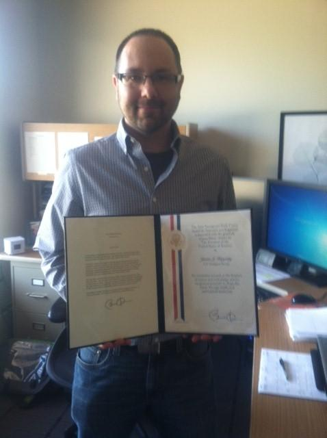 Dr. Justin Hagerty shows off his science award, freshly signed by President Obama.