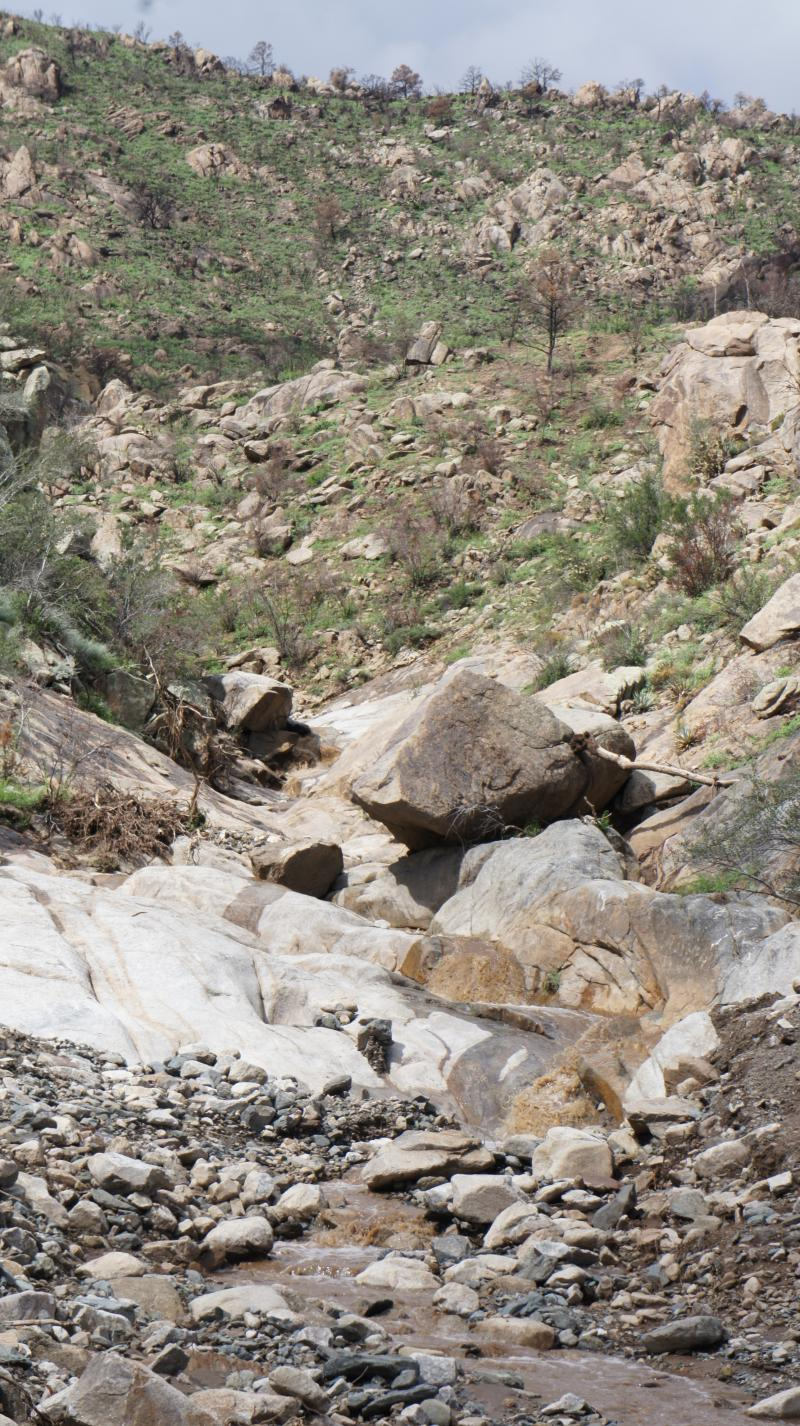 A large boulder the size of a small car teeters on the edge of an arroyo where it was deposited by heavy water flows that started with monsoon season.