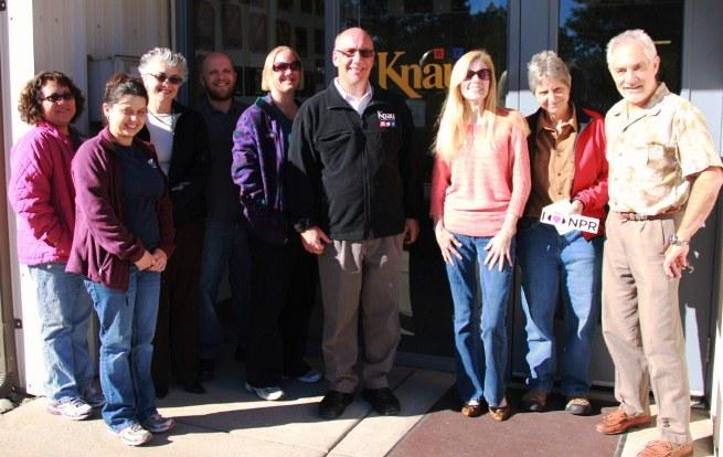 W.L. Gore morning shift volunteers, with KNAU General Manager, John Stark, and Morning Edition Host, Janice Baker, (pictured to the left and right of KNAU window logo).