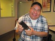 Garrickson Begay demonstrates how he uploads his weight, blood pressure and blood oxygen level into his smart phone.