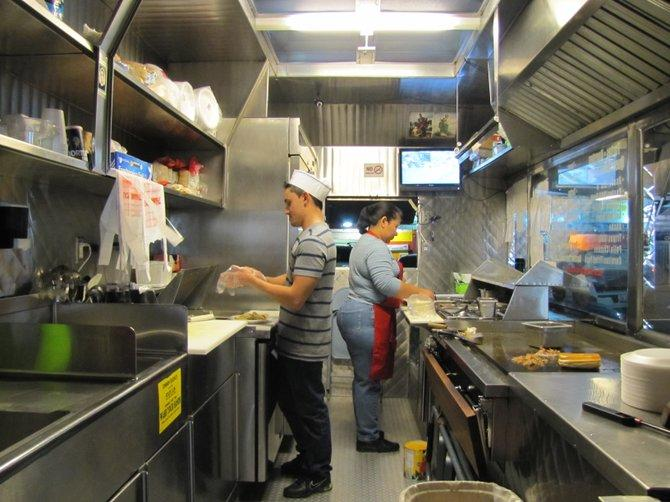 Employees at work inside the Tacos La Doña taco truck.