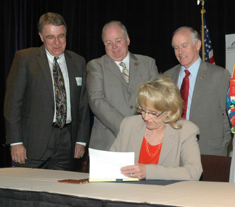 Gov. Jan Brewer signs legislation Friday with a package of tax cuts for business she said will stimulate the economy. Looking on are Sen. Steve Yarbrough, House Speaker Andy Tobin and Senate President Steve Pierce.
