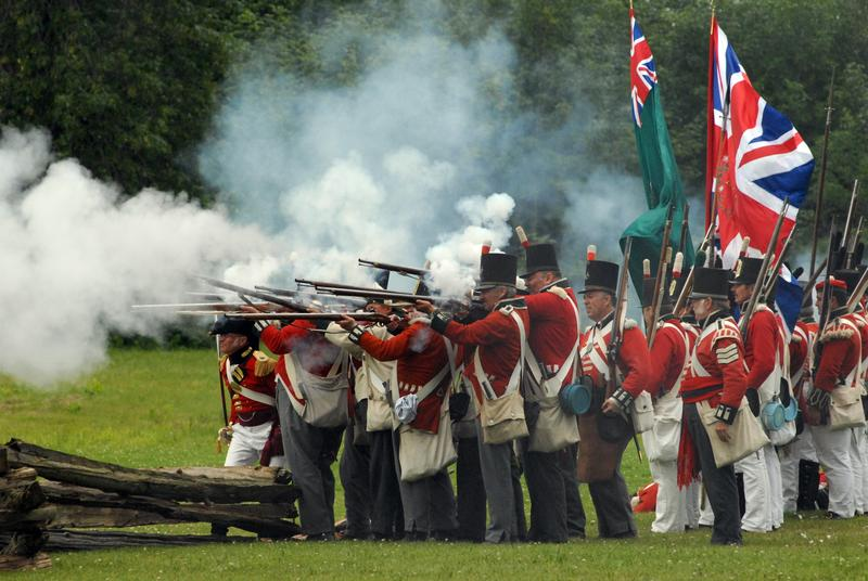 "British in firing formation letting loose the ""fog of war,"" in a re-enactment from The War of 1812."