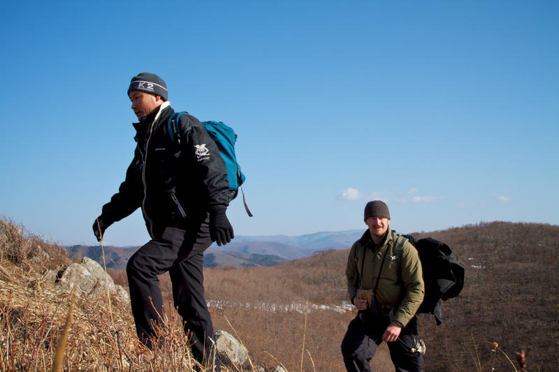 Chris Morgan and Korean filmmkaer Sooyong Park walk from the snowy valleys to a sun bathed ridge top in their search for signs of a Siberian tiger in Lazovsky Zavopednik, Primorsky Krai, Russia.