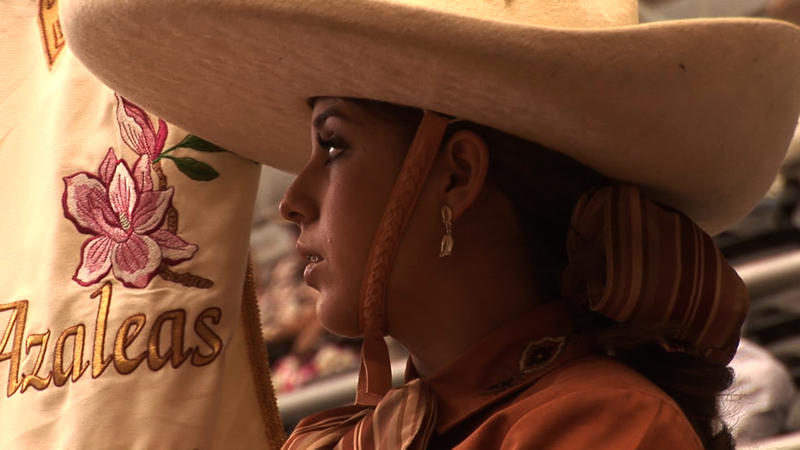 Escaramuza Charra Las Azaleas member Vanessa Garcia proudly carries the team banner at the National Charro Championships in Guadalajara, Jalisco, Mexico.