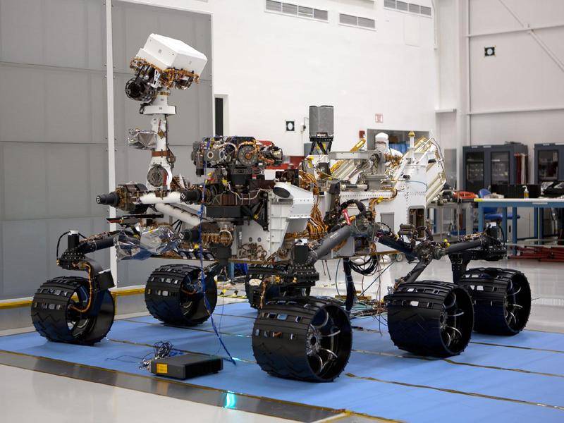 In the Payload Hazardous Servicing Facility at NASA's Kennedy Space Center in Florida, the robotic arm of the Mars Science Laboratory (MSL) rover, Curiosity, has been stowed against the body of the spacecraft.
