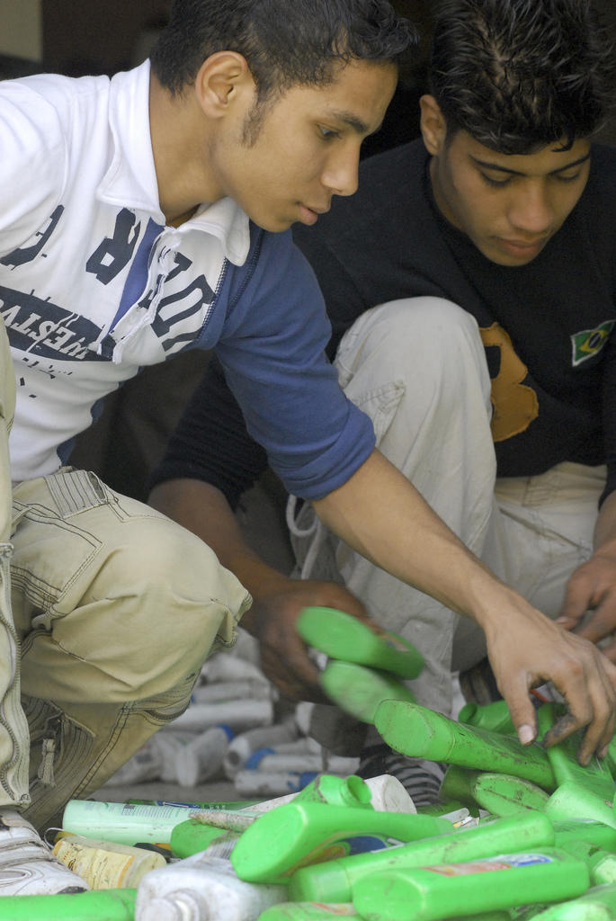 Adham and Nabil sorting shampoo bottles at the Recycling School.