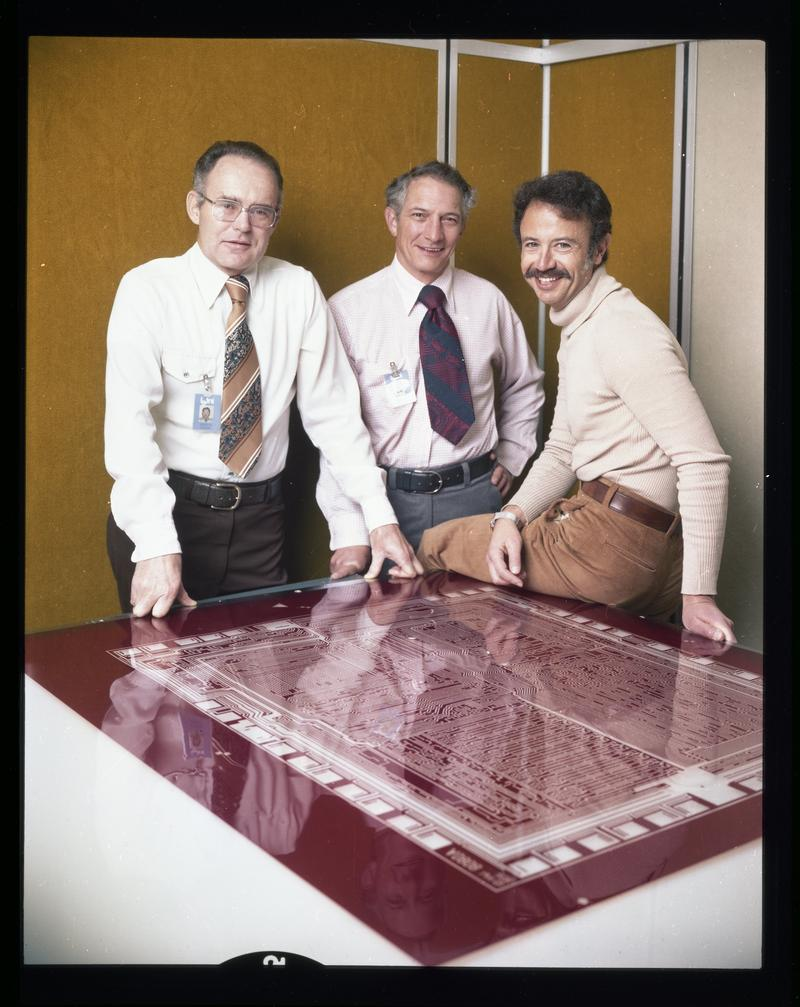 Intel executives Robert Noyce, Gordon Moore, and Andy Grove standing over a mask design on 10th anniversary of Intel.