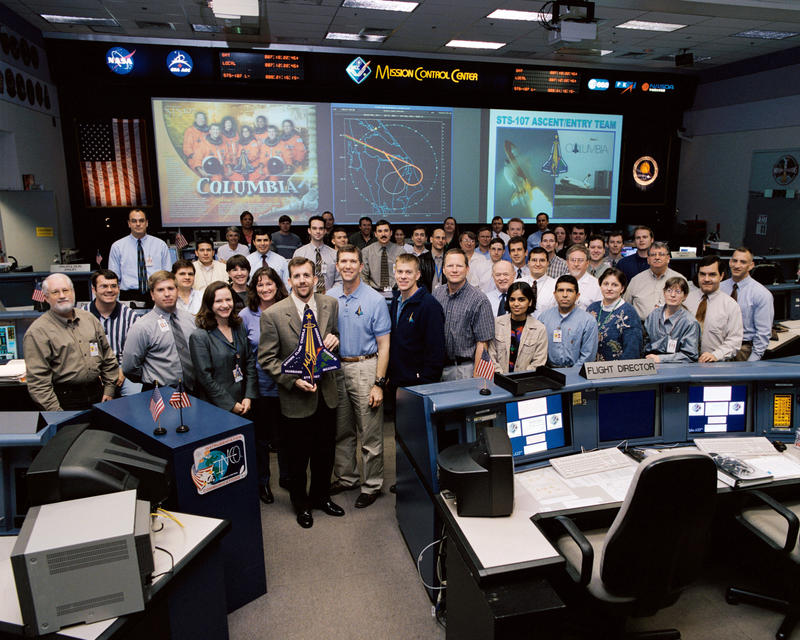 The members of the STS-107 Ascent/Entry team pose for a group portrait in the shuttle flight control room in Houston's Mission Control Center. Flight director LeRoy Cain holds the STS-107 mission logo.
