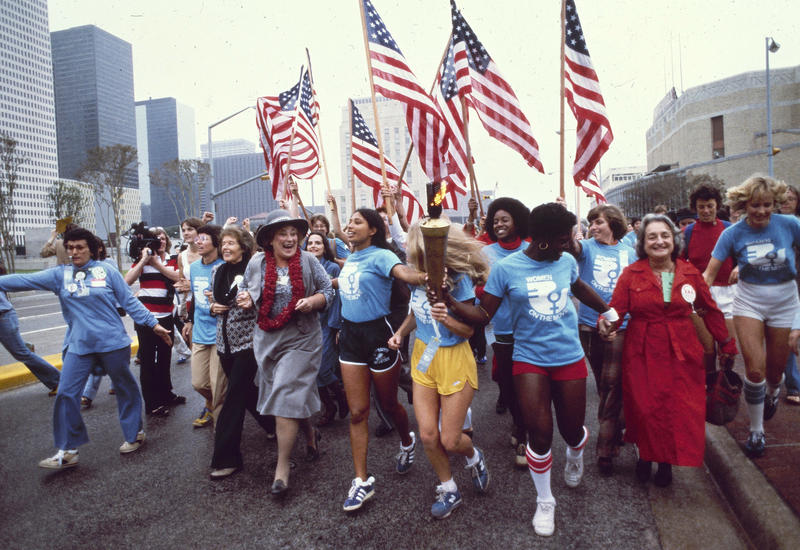 Leaders of the Women's Movement pass a torch that was carried by foot from New York to Houston, Texas, for the National Women's Convention.