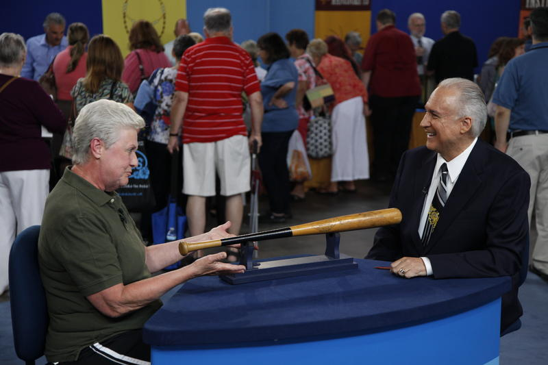 Mike Gutierrez (right) with a guest and a bat used by Mickey Mantle.