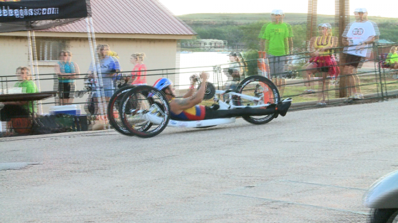 A handcyclists bikes up the hill.