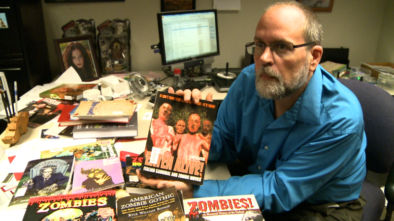 Rob Weiner holds up a book about zombies.