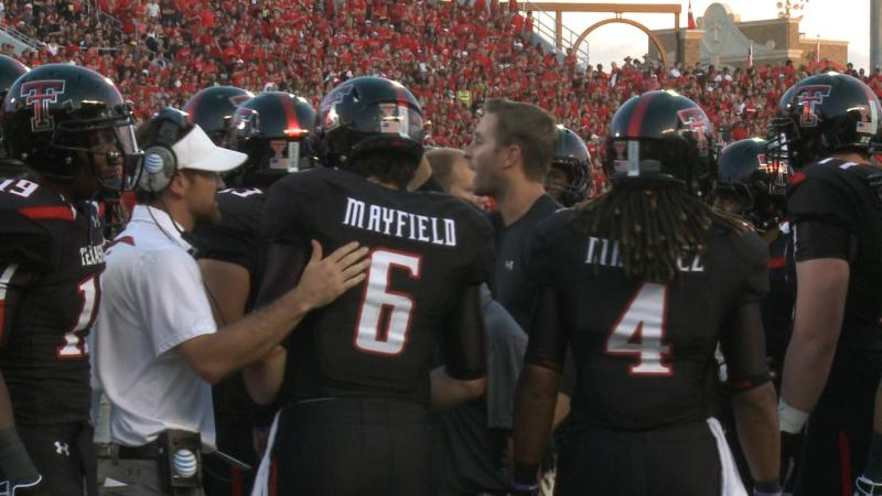 Kliff Kingsbury talks with his team during the game.