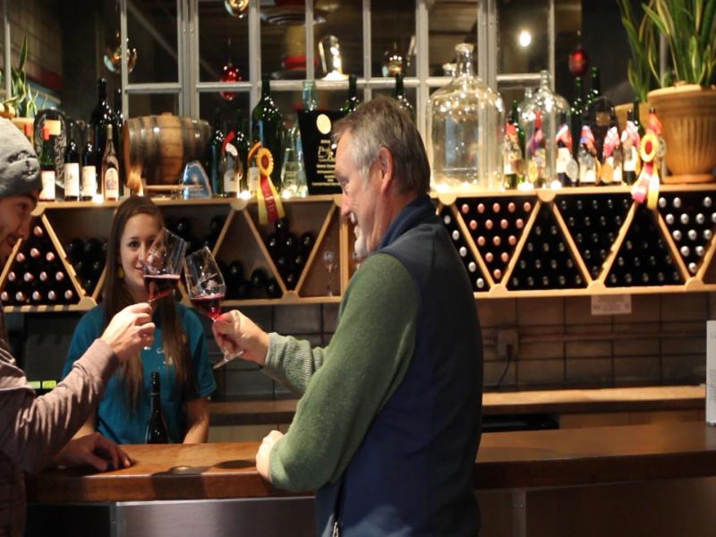 Kim McPherson enjoys some wine in his tasting room.