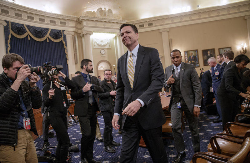 FBI Director James Comey takes a break after three hours of testifying on Capitol Hill on Monday.