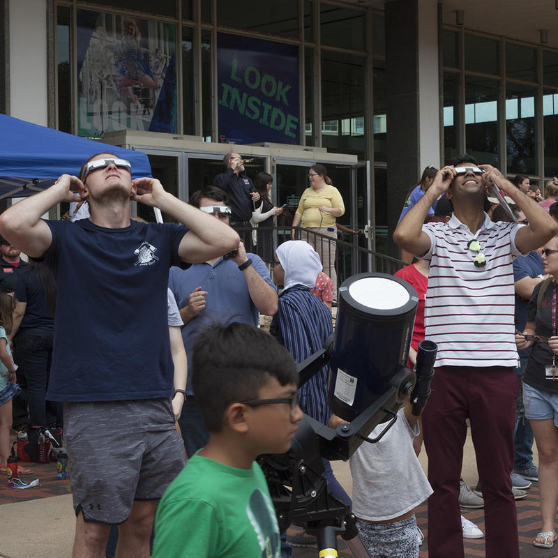 Spectators gaze up as the eclipse breaks its way through the cloud coverage.