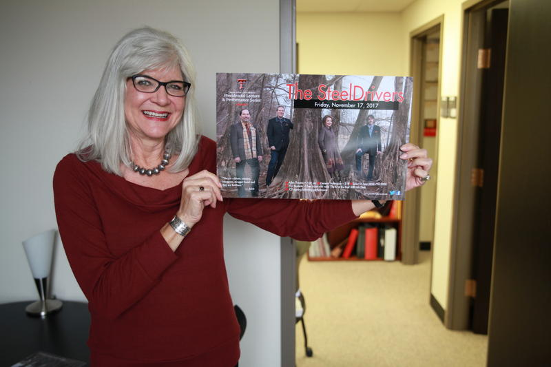 Jo Moore holds the poster for The Steeldrivers' upcoming performance.