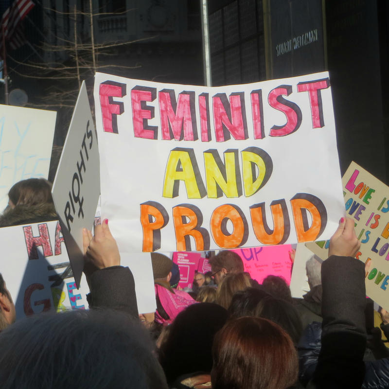"Demonstrators wave a ""Feminist and Proud"" sign during a protest."