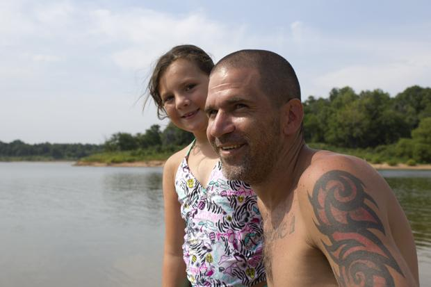 Shaun Pelkey and his daughter Ireland Pelkey enjoy the afternoon at one of Walnut Creek State Park's beaches on Keystone Lake.