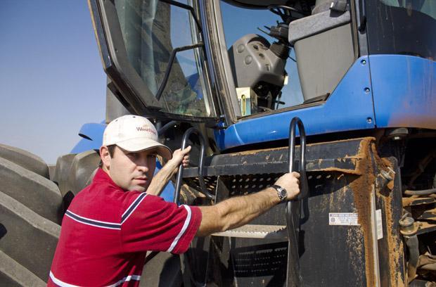 Mason Bolay climbs into the cab of a tractor on his family's farm near Perry, Okla.