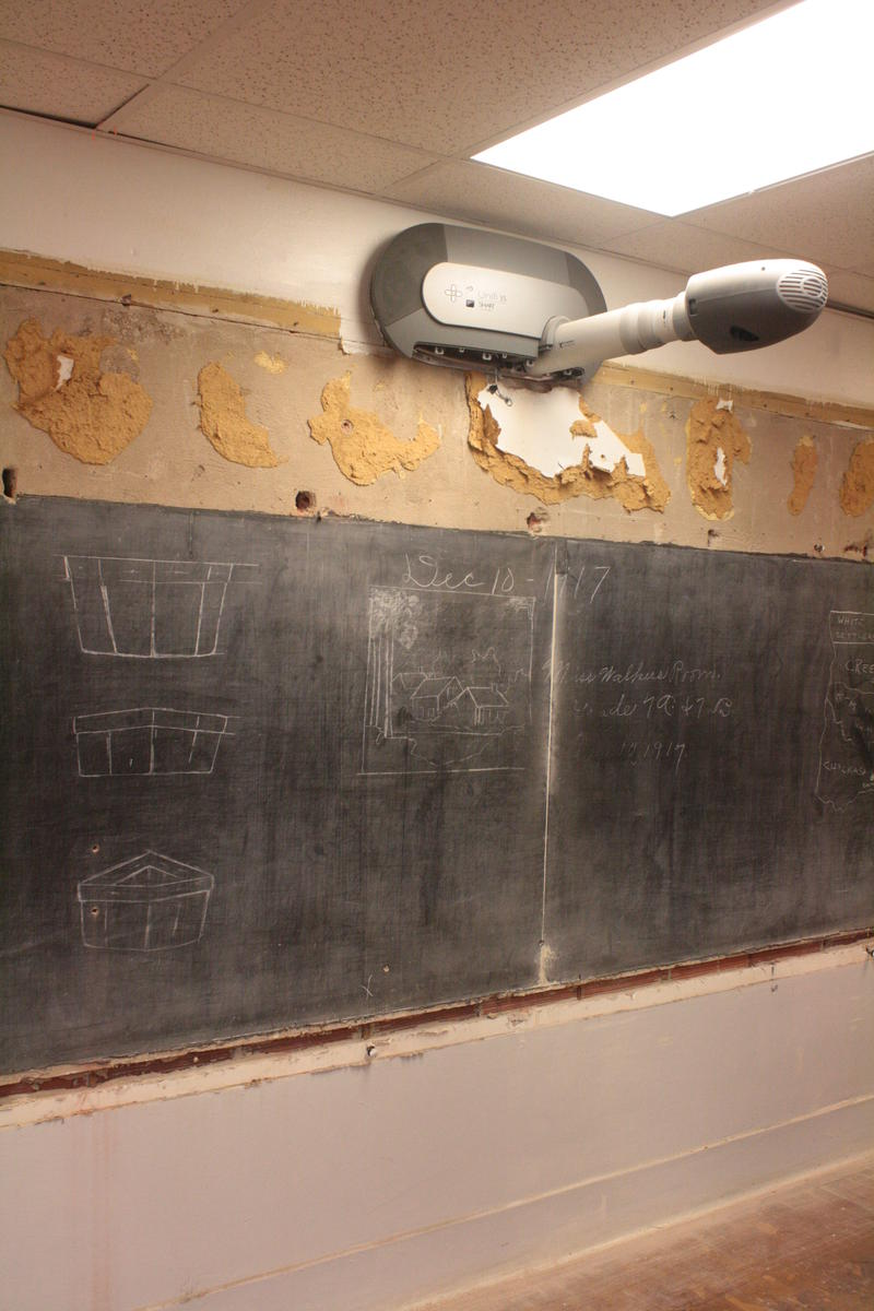 A Smart Board projector, which is very modern technology, hanging over 100-year-old chalkboards.