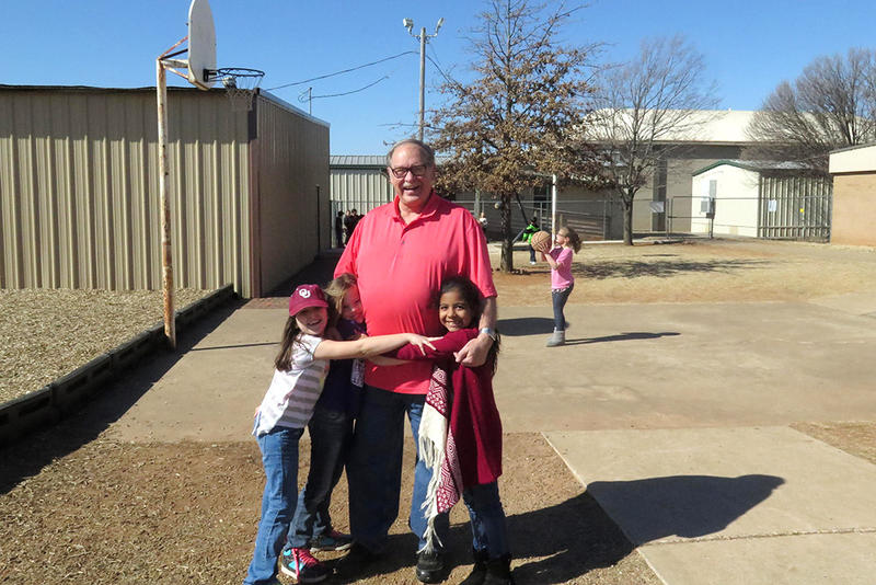 Superintendent of Friend School, Alton Rawlins, hangs out with some of his students on the playground.