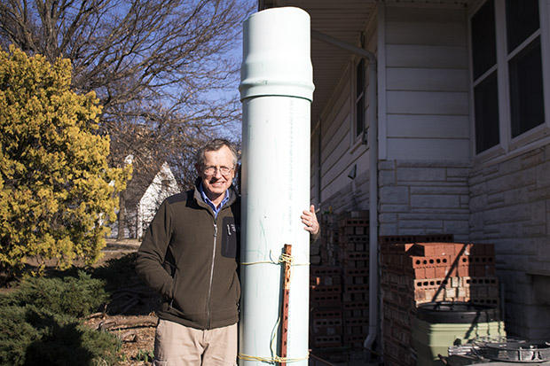 Jack Romine stands near a makeshift chimney state inspectors installed over an abandoned, leaky well that was discovered near his home in Bartlesville, Okla.
