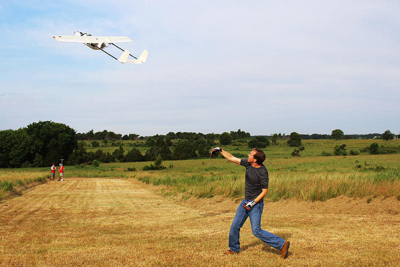 A researcher launches an unmanned aerial vehicle in the field to collect weather data.